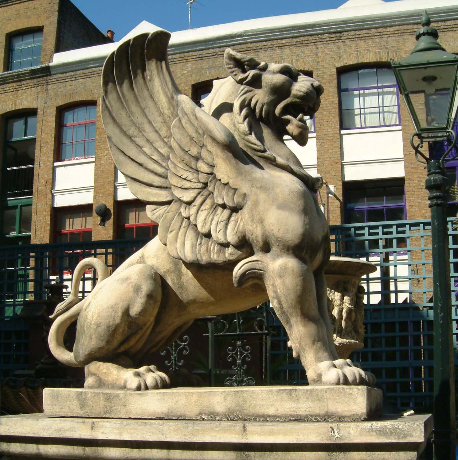 A massive French reconstituted stone winged lion-0
