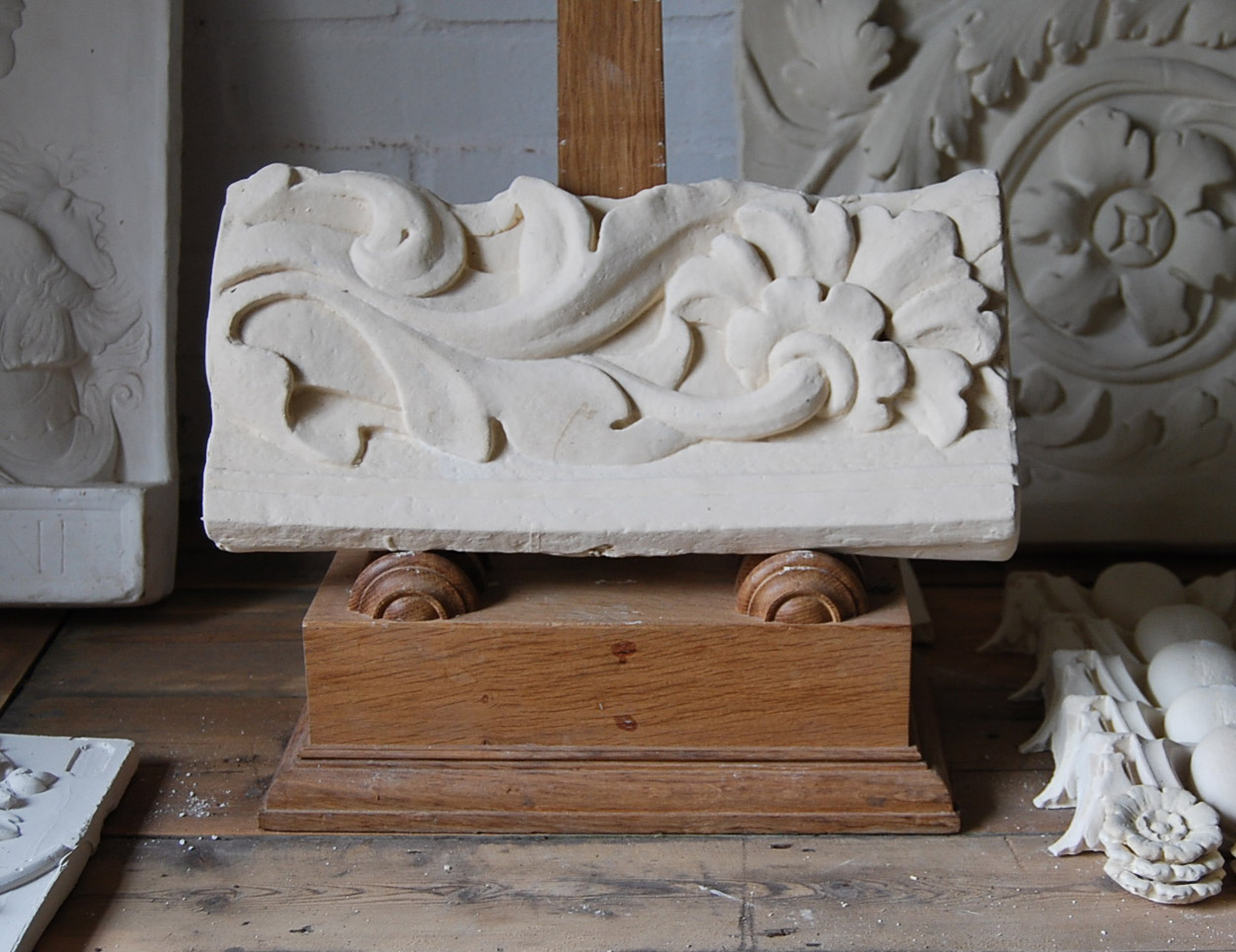 A cast plaster relief of a stylised flower and stem-0