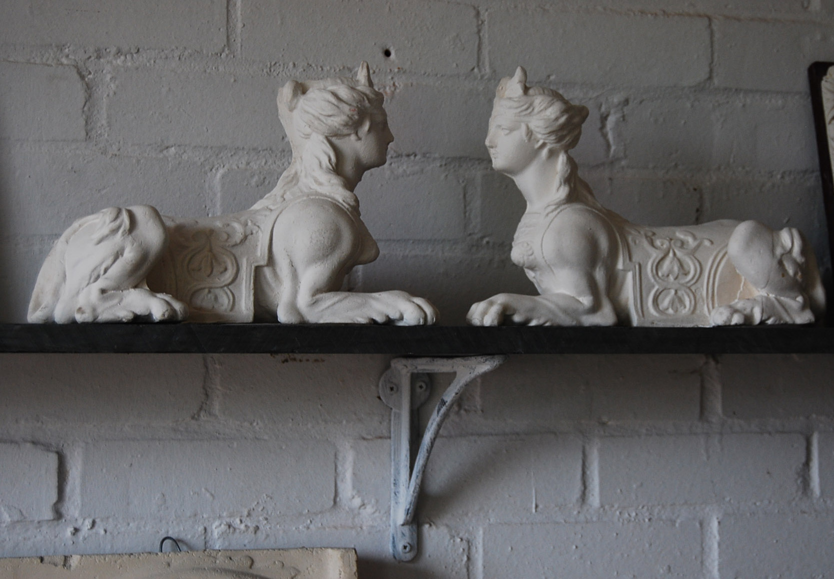 A pair of plaster Sphinx, cast in relief-0