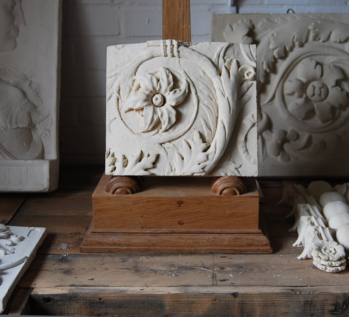 A cast plaster relief of a flowerhead and frond leaf scroll-0