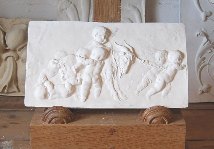 An English relief cast plaster plaque of Putti with a goat-0