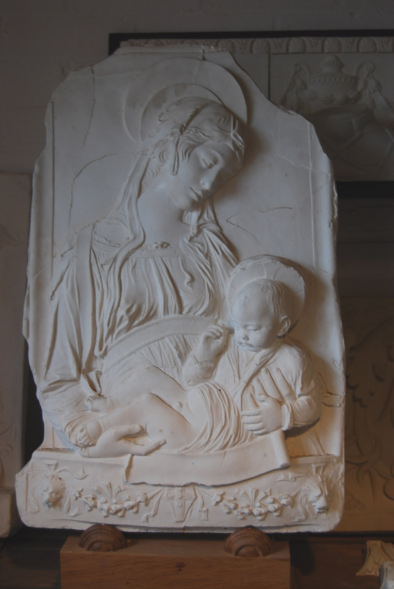 An English cast plaster relief of the Madonna and Child,-0
