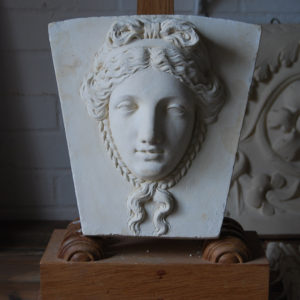 A cast plaster keystone with a classical head of a maiden-0