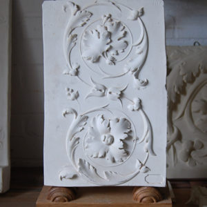 A cast plaster section of open scroll frieze-0