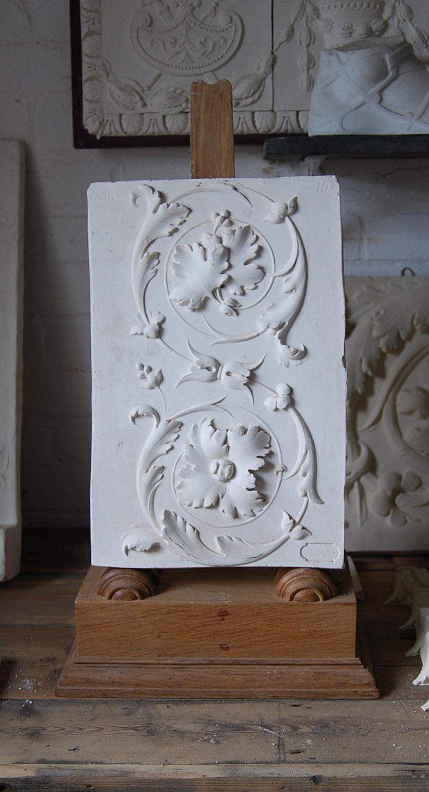 A cast plaster section of open scroll frieze-0