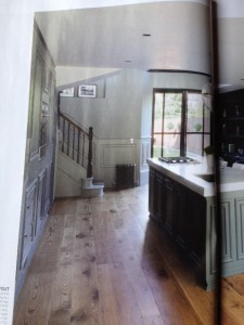 The aged oak flooring works perfectly in the large open plan kitchen and offsets the painted cabinetry as well as the salvaged radiator at the foot of the stairs.