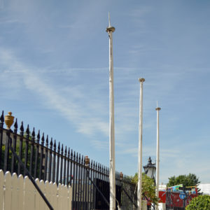 A set of three wooden flagpoles,-0