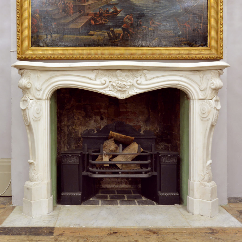 A Rococo Revival white Carrara marble chimneypiece