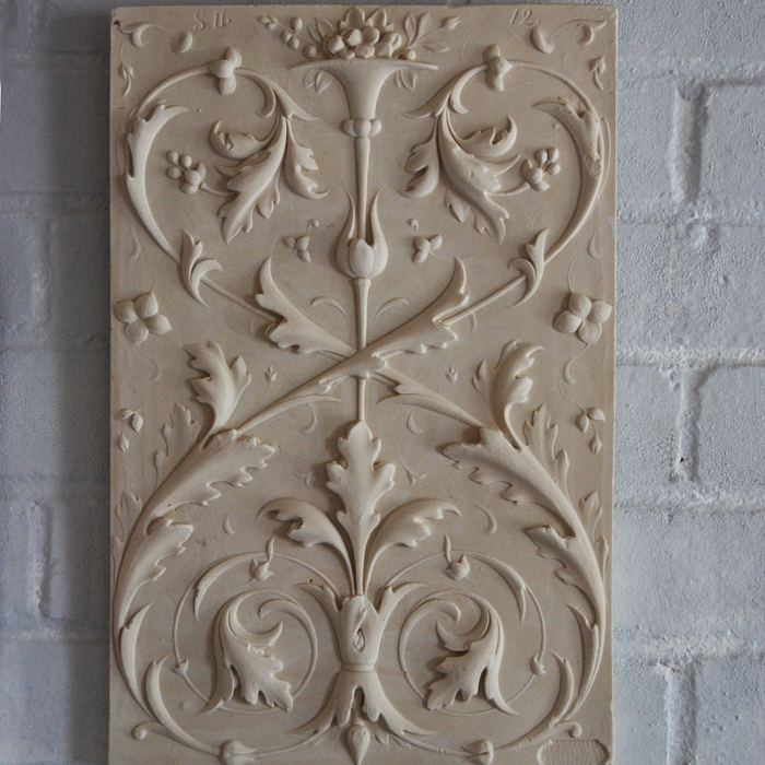 A relief-cast plaster plaque of opposed foliate scrolls,-0