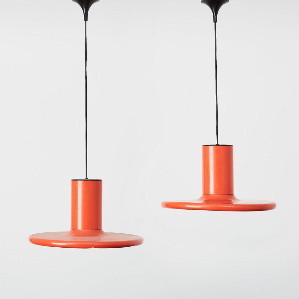 A pair of orange pendant lights by LITA,-0