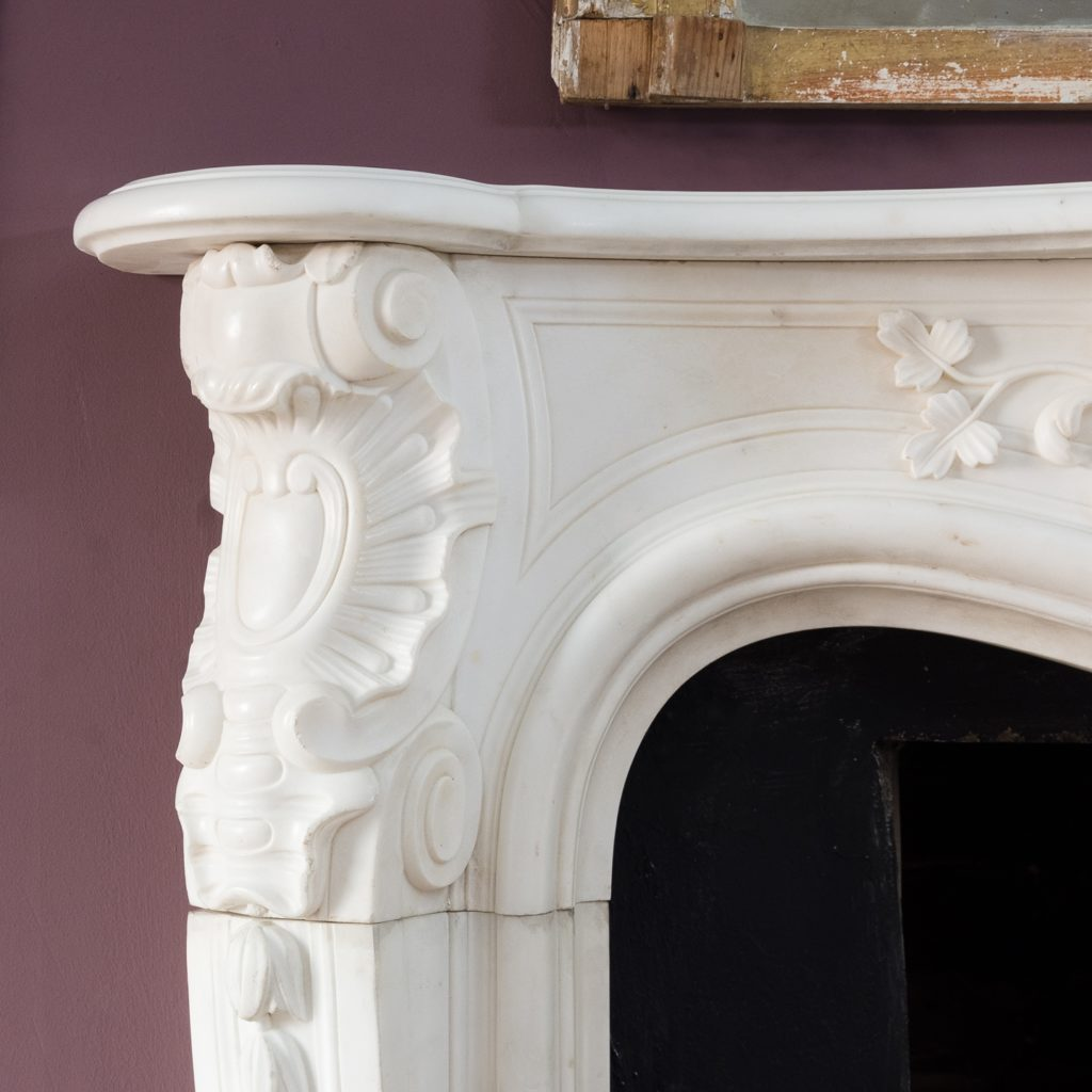 canted volute jambs headed by richly carved rocaille cabochon and c-scrolls above trailing bell-flowers