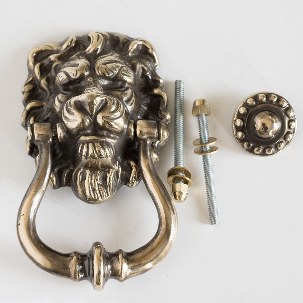 Brass lion's mask door knocker with striking plate and fixing bolts