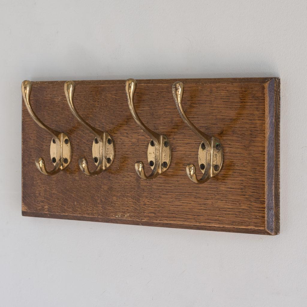 Set of four mounted brass coat hooks,-0