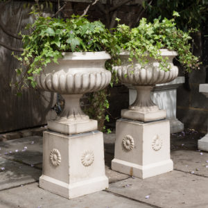 Pair of Victorian glazed terracotta tazza urns with pedestals,