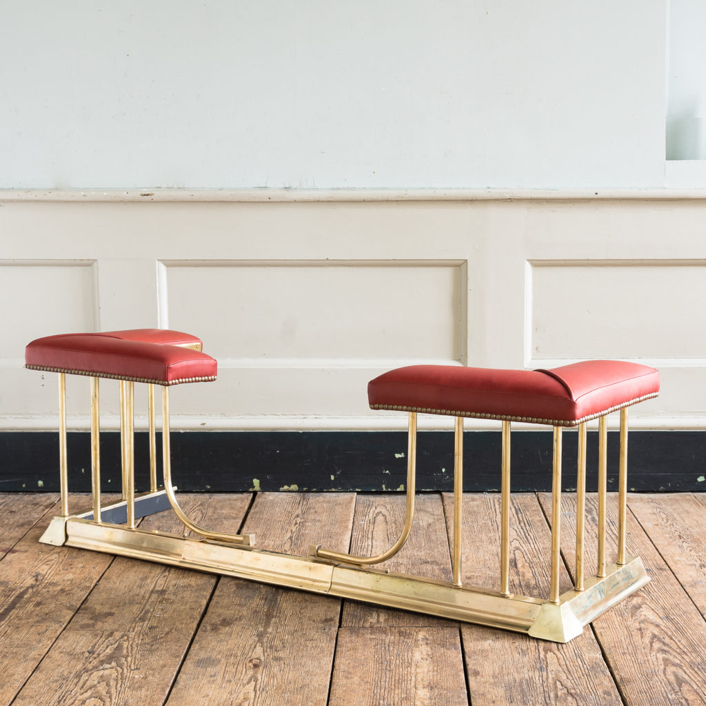 Twentieth century brass and leather upholstered club fender,