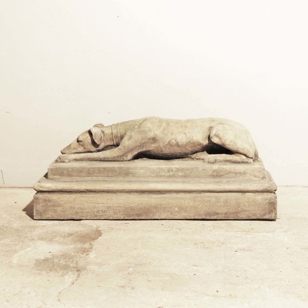 An English composition stone recumbent whippet on plinth-0