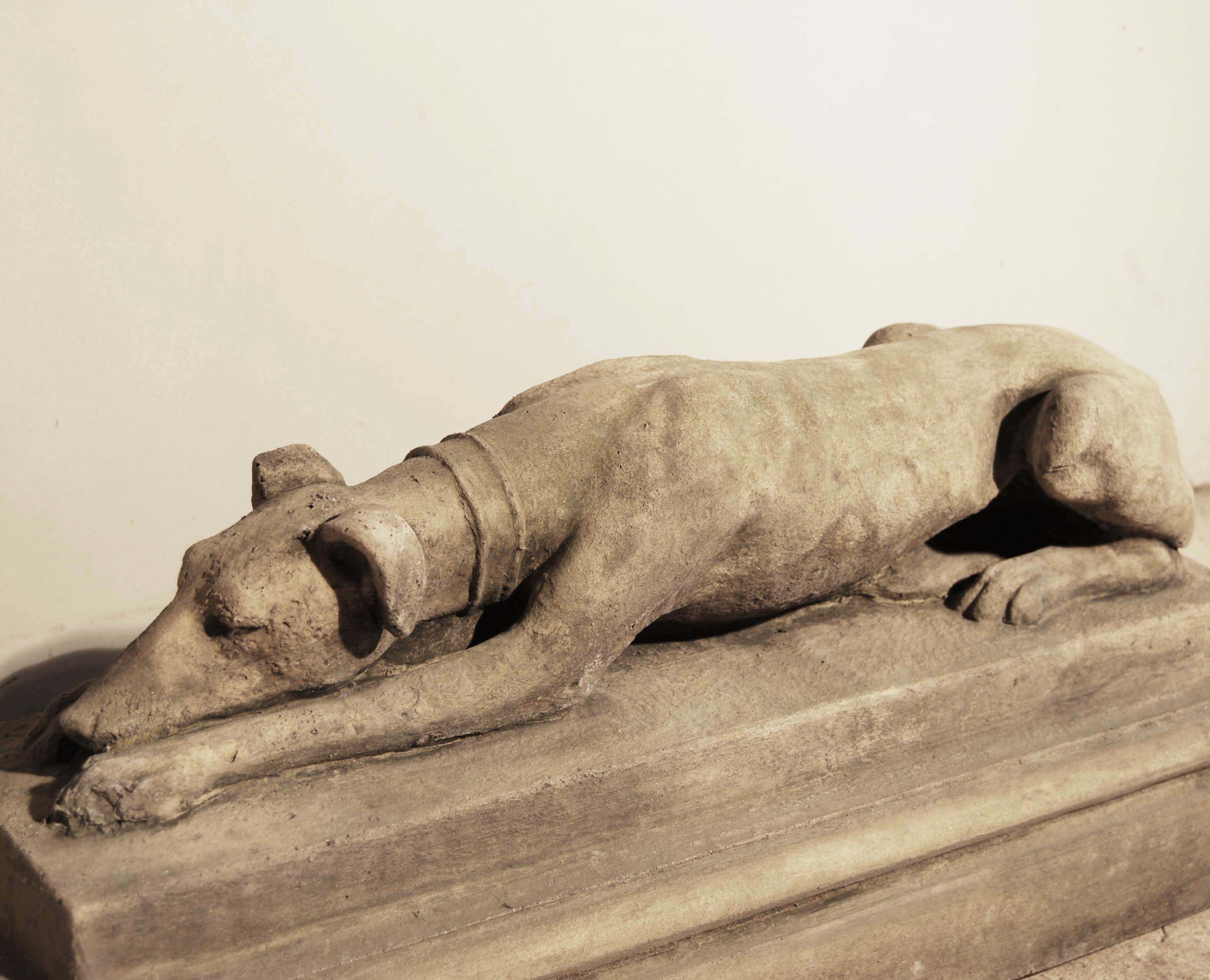 An English composition stone recumbent whippet on plinth-134579