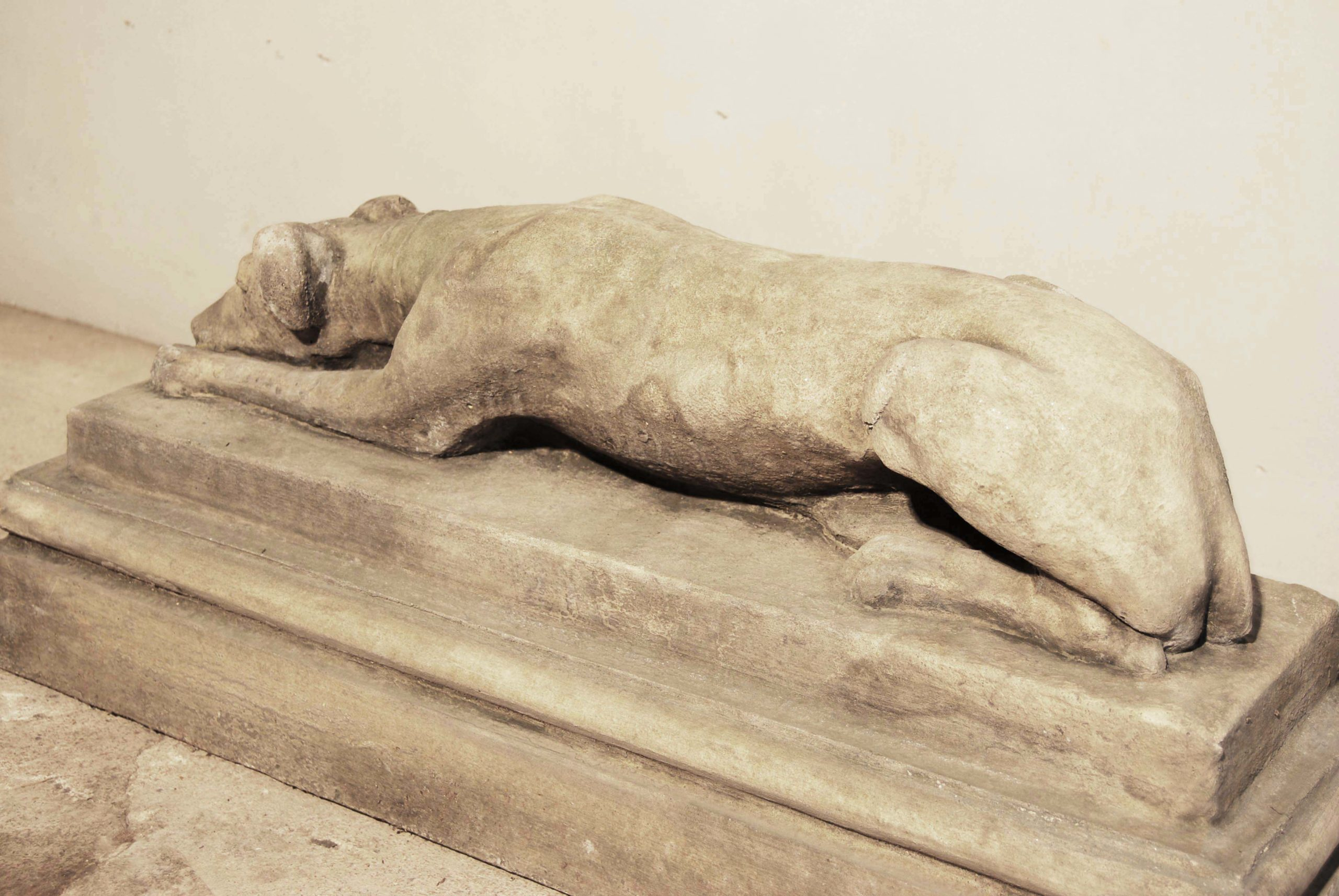An English composition stone recumbent whippet on plinth-134580