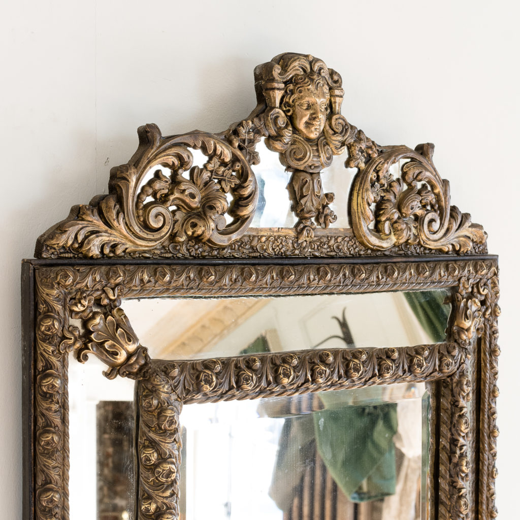 the cresting of scrolled acanthus and cherub mask in the Baroque manner,