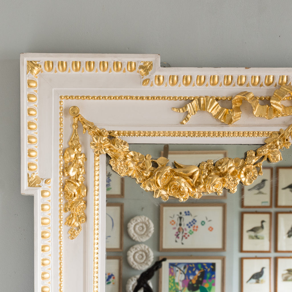 the egg and dart bordered frame hung with foliate festoons.