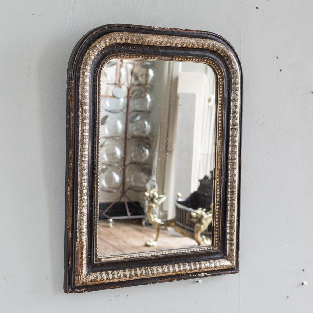 French ebonised and parcel silver-gilt wall mirror,